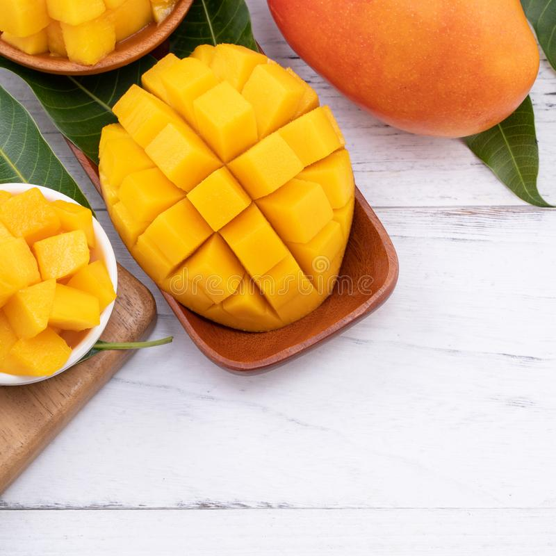 Fresh chopped mango on a tray and bright rustic wooden background. Tropical summer fruit design concept, close up, macro, copy stock images
