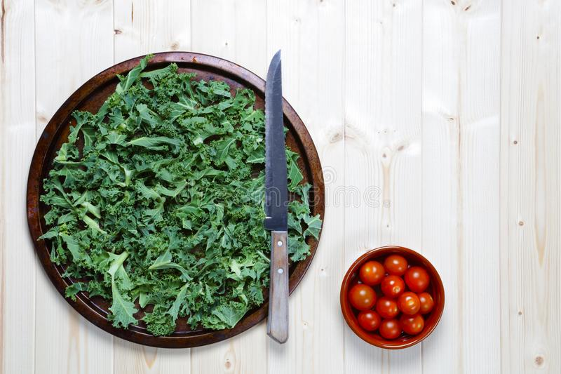 Fresh chopped prepared kale with bowl of cherry tomatoes stock photos