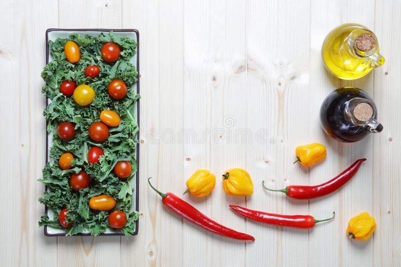 Fresh chopped prepared kale with cherry tomatoes and peppers stock images
