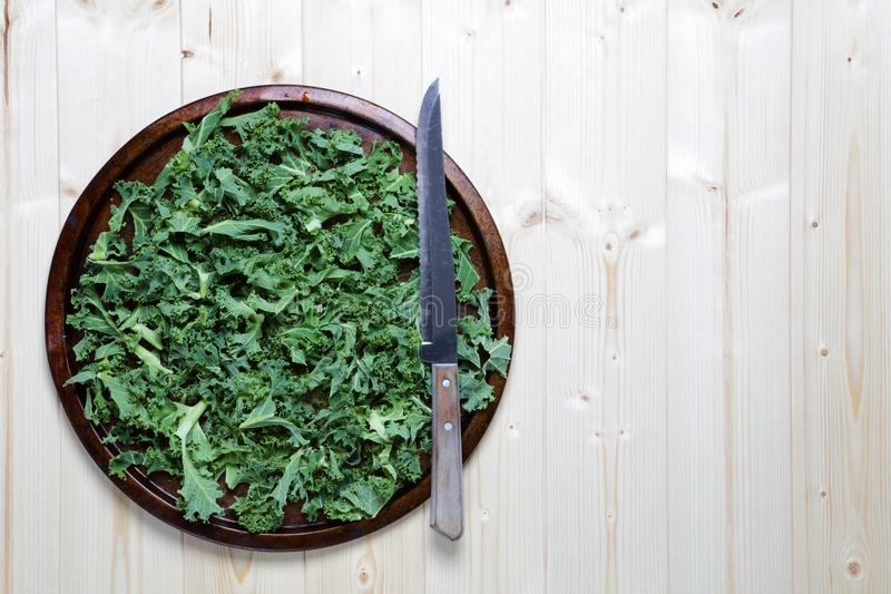 Fresh chopped prepared kale with knife stock images