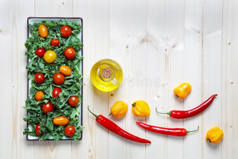 Fresh chopped prepared kale with tomatoes peppers and olive oil stock images