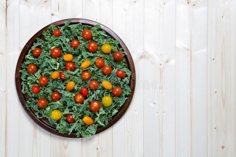 Fresh chopped prepared kale with yellow and red cherry tomatoes royalty free stock photography