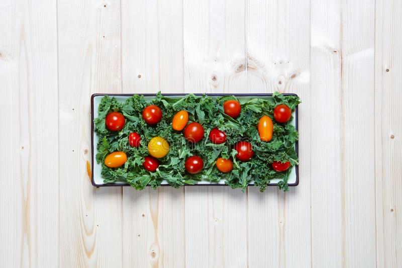 Fresh chopped prepared kale with yellow and red cherry tomatoes on plate stock photos