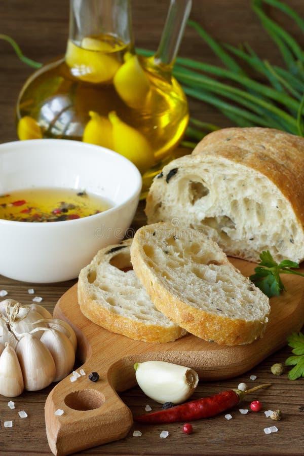 Fresh ciabatta. Homemade ciabatta, garlic olive oil and spices on a wooden board royalty free stock photos