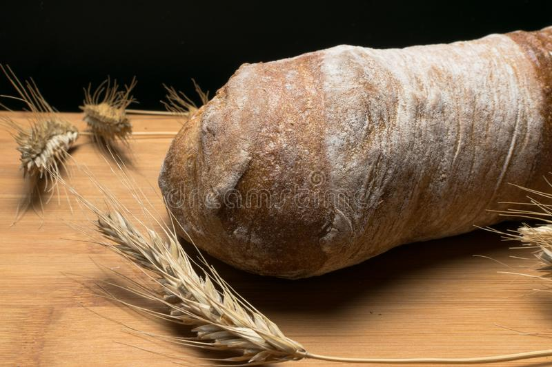 fresh ciabatta bread on wooden table with ears of wheat royalty free stock photo