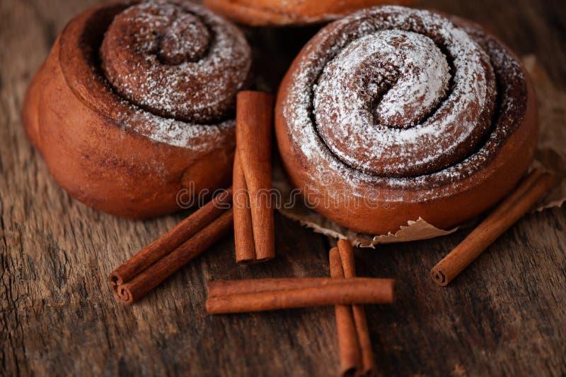 Fresh cinnamon buns on wooden background. Sweet cinnamon rolls. Fresh cinnamon buns on wooden background. Sweet cinnamon rolls stock photography