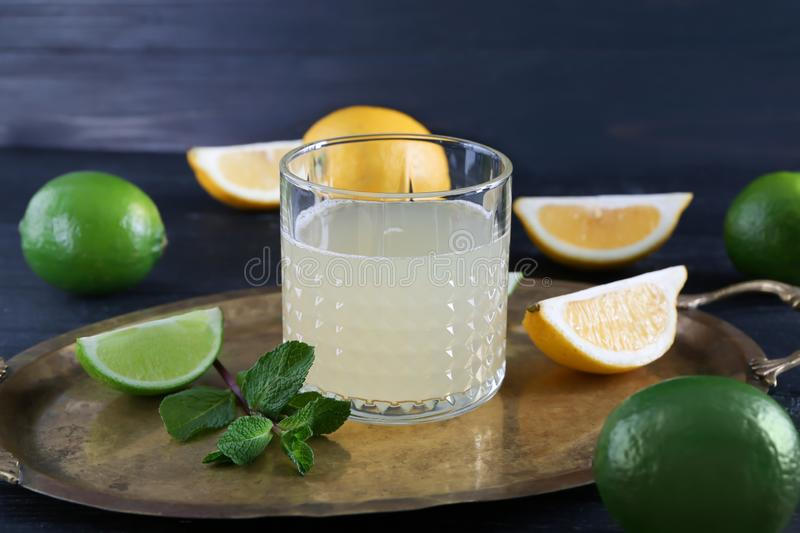 Fresh citrus drink in glass and sliced fruits on tray royalty free stock image