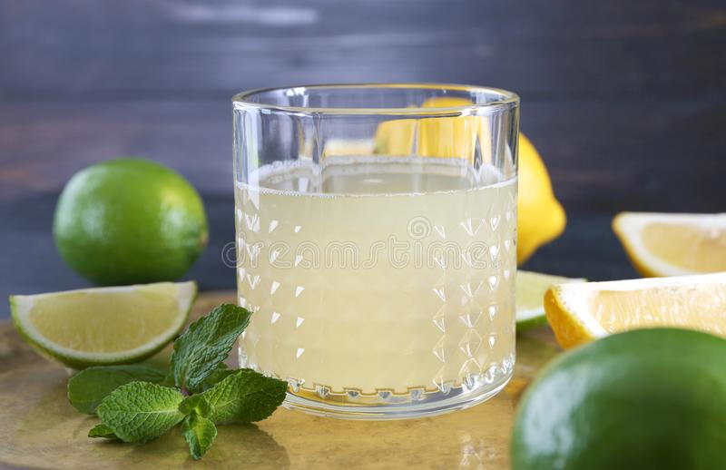 Fresh citrus drink in glass and sliced fruits on tray royalty free stock photography