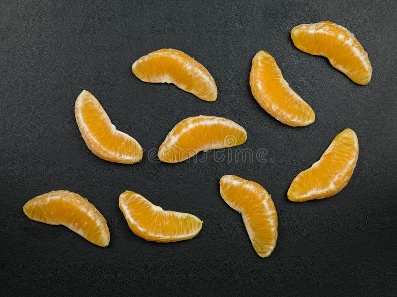 Fresh Citrus Fruit Orange Segments. Against a Black Background stock photos