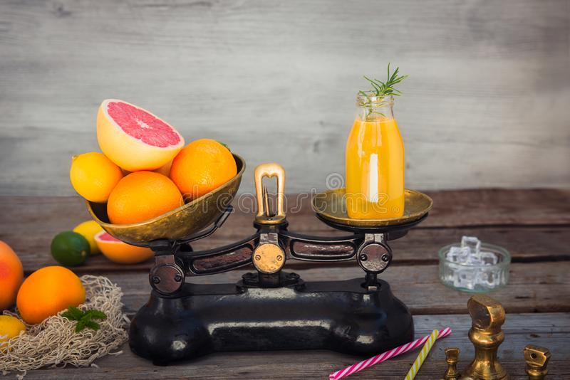 Fresh citrus fruits on the one scalepan of vintage weights and homemade juice on the other. Equivalent healthy value. Clean detox stock photography