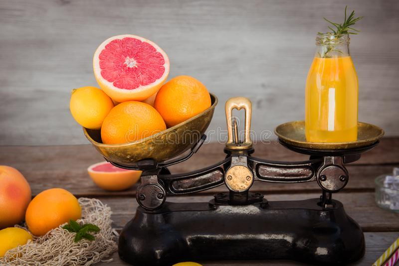 Fresh citrus fruits on the one scalepan of vintage weights and homemade juice on the other. Equivalent healthy value. Clean detox royalty free stock photography