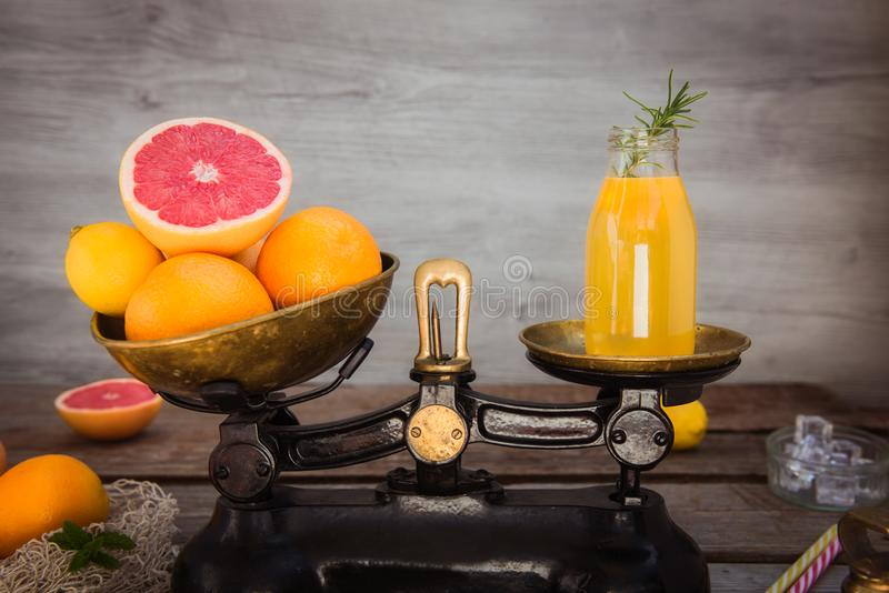 Fresh citrus fruits on the one scalepan of vintage weights and homemade juice on the other. Equivalent healthy value. Clean detox royalty free stock photos