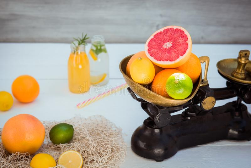 Fresh citrus fruits in vintage scale and several oranges, lemons, grapefruit, lime and homemade drinks on the white wooden table royalty free stock image