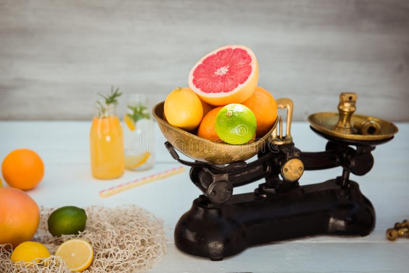 Fresh citrus fruits in vintage scale and several oranges, lemons, grapefruit, lime and homemade drinks on the white wooden table royalty free stock photography