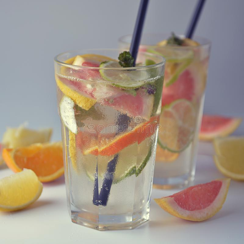 Fresh citrus infused flavored lemonade. Refreshing summer homemade cocktail with lemon, lime, orange and grapefruit. Square image stock photography