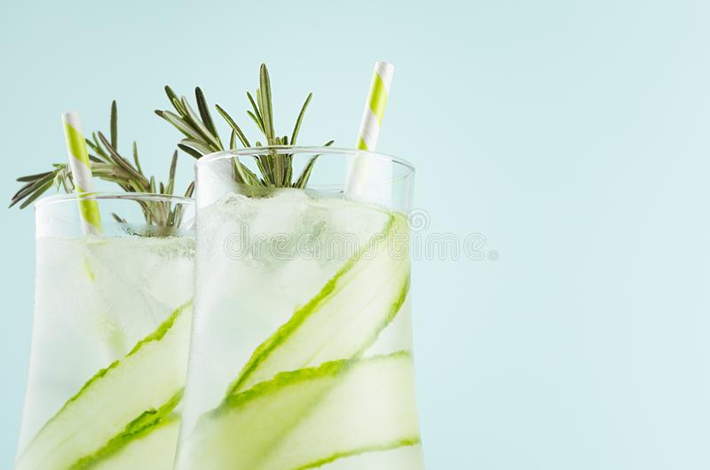 Fresh citrus muddy lemonade with ice cubes, straw, rosemary in elegant misted glasses on soft light green background, closeup. Fresh citrus muddy lemonade with royalty free stock photos