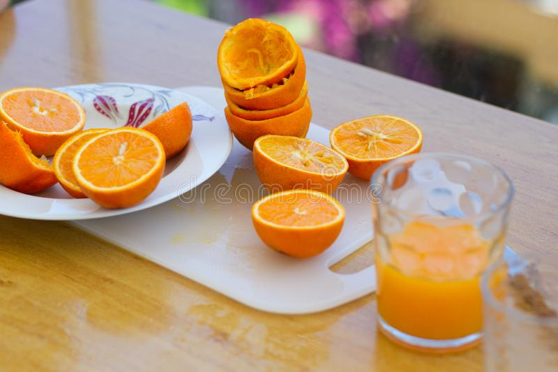Fresh citrus orange halves on the plate and cuttimg board after making orange juice royalty free stock images