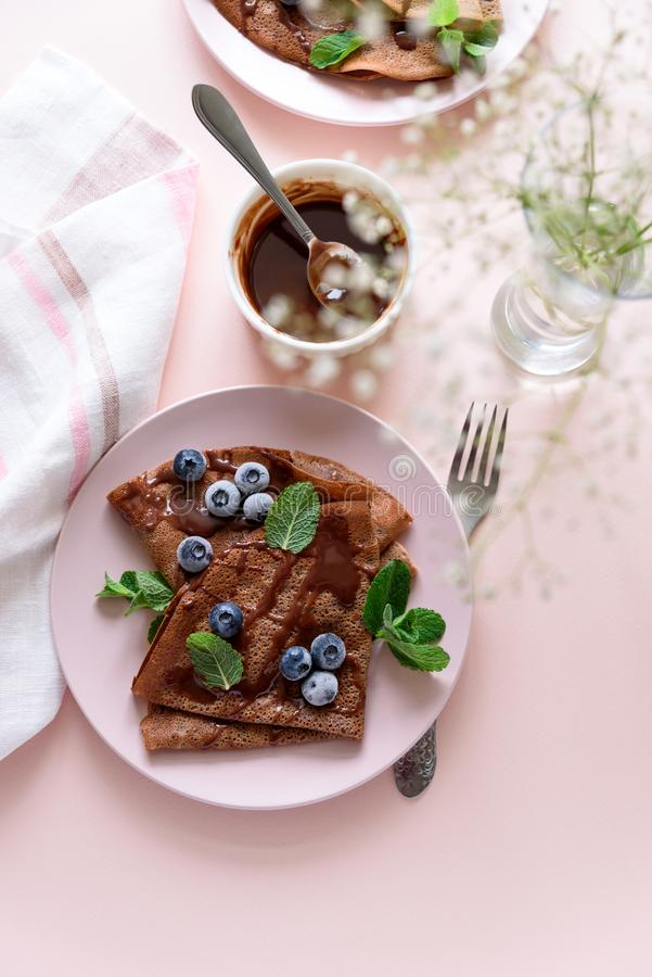 Homemade chocolate crepes served with blueberries, sauce and mint leaves on pink background. Selective focus. Top view. Copy space.  royalty free stock photos
