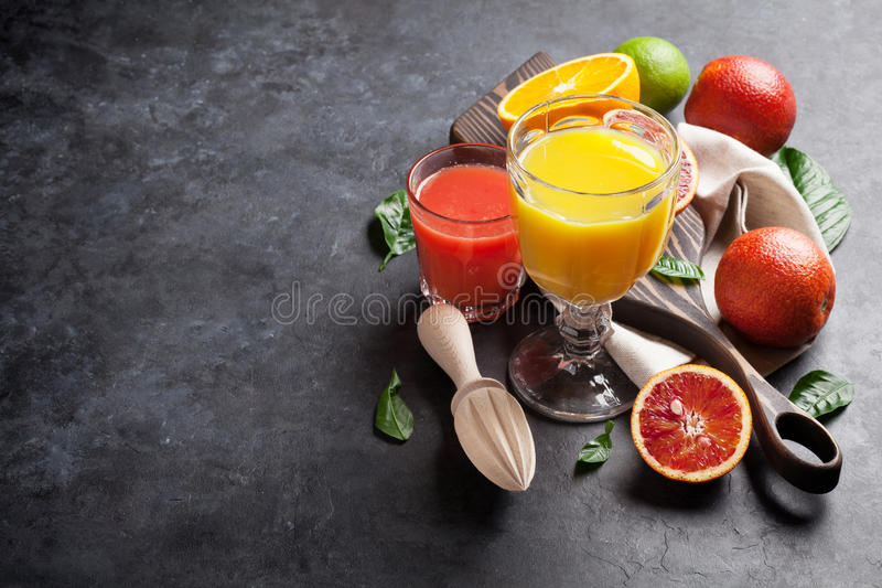Fresh citruses and juice. On dark stone background. Oranges and limes. View with copy space royalty free stock images