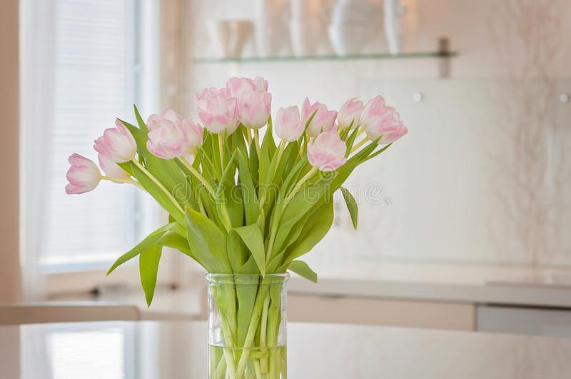 A fresh and clean home office with soft pink tulip flowers in a kitchen for Women`s Day celebration. Airy Scandinavian/Nordic. Interior style on a media office stock photography