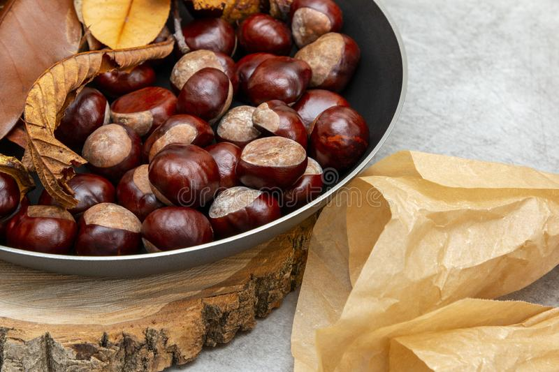 Fresh clean shiny chestnuts in a pan with autumn foliage and paper parcels stock photo
