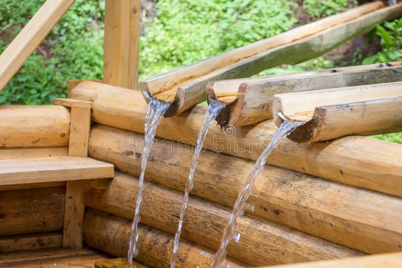 Fresh clean spring. water run through wooden gutters.  stock photo