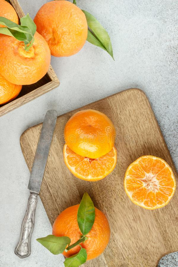Fresh clementines on board with green leaves with a knife. Top v stock photography