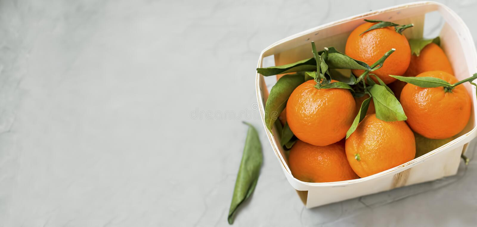 Fresh clementines citrus fruits in a basket with copy space, healthy organic clementines with leaves top view in a basket on royalty free stock images
