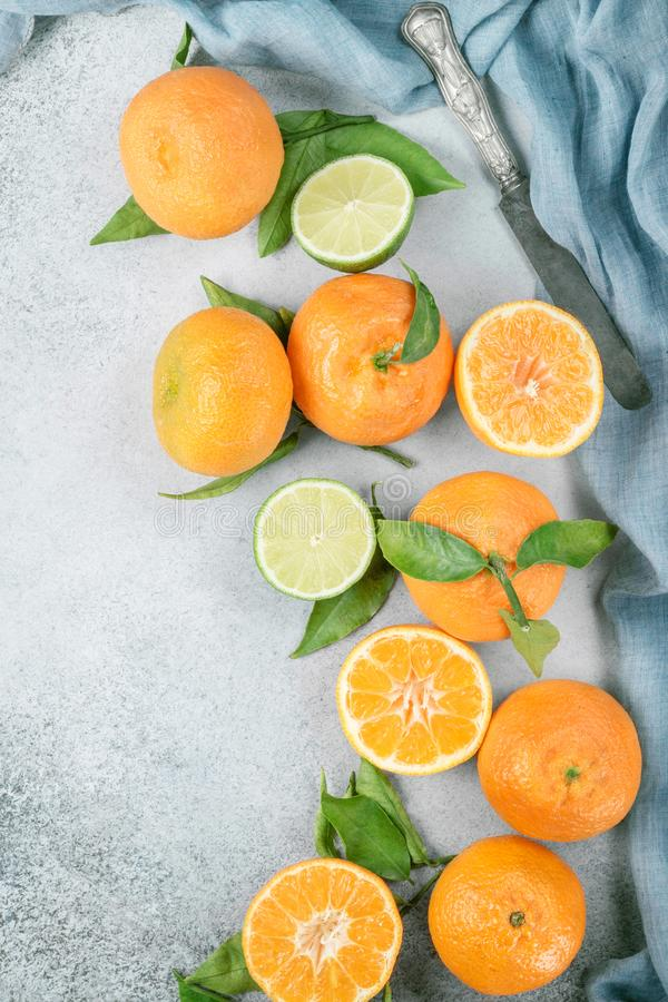 Fresh clementines with green leaves and lime with a knife. stock photography