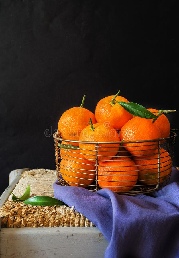 Fresh clementines, in a metellic basket on black background. Some clementines, in a metellic basket on black background royalty free stock images
