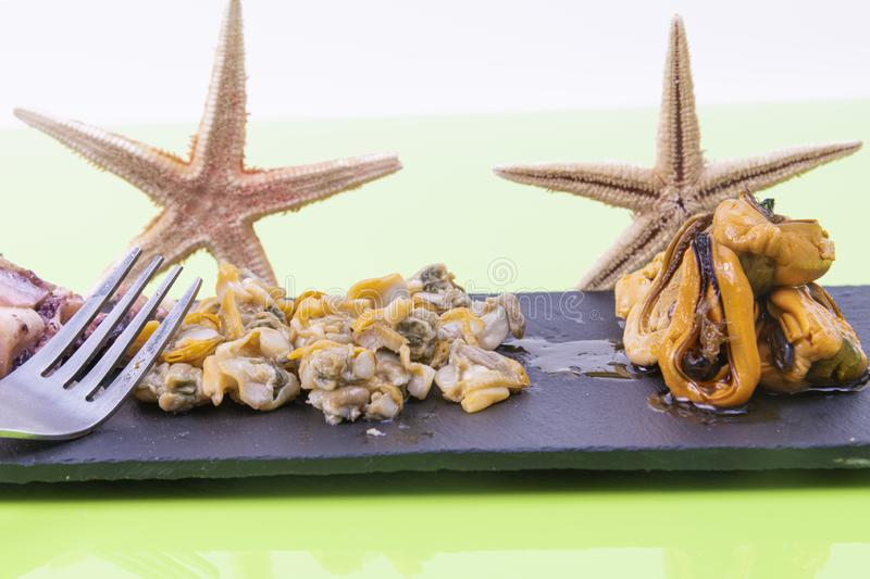 Fresh cockles and pickled mussels served on a black stone table adorned with a couple of starfish. stock photo
