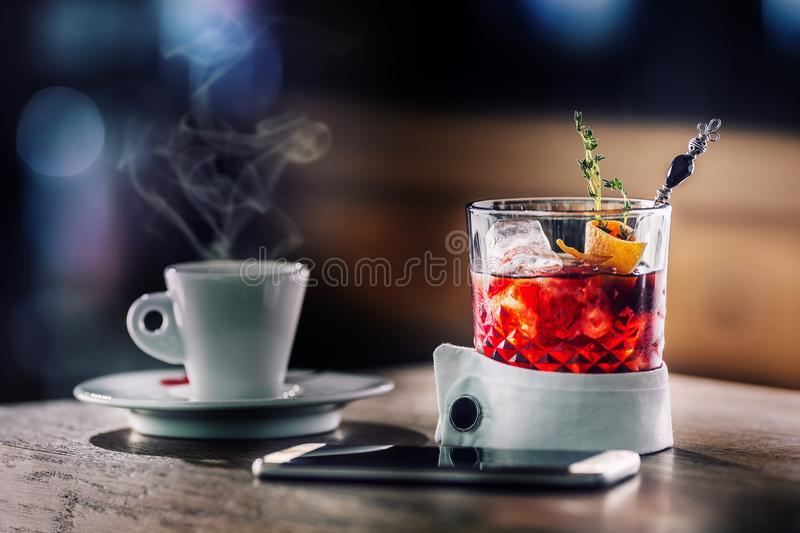 Fresh cocktail drink with cup of coffee and smartphone. Alcoholic, non-alcoholic drink-beverage at the bar counter in the pub. royalty free stock photography