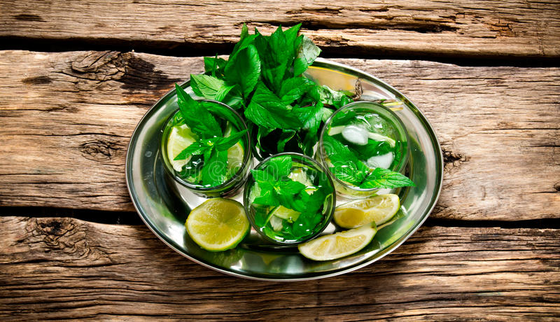 Fresh cocktail of lime, mint, rum and ice on a metal tray . On a wooden table. royalty free stock photo