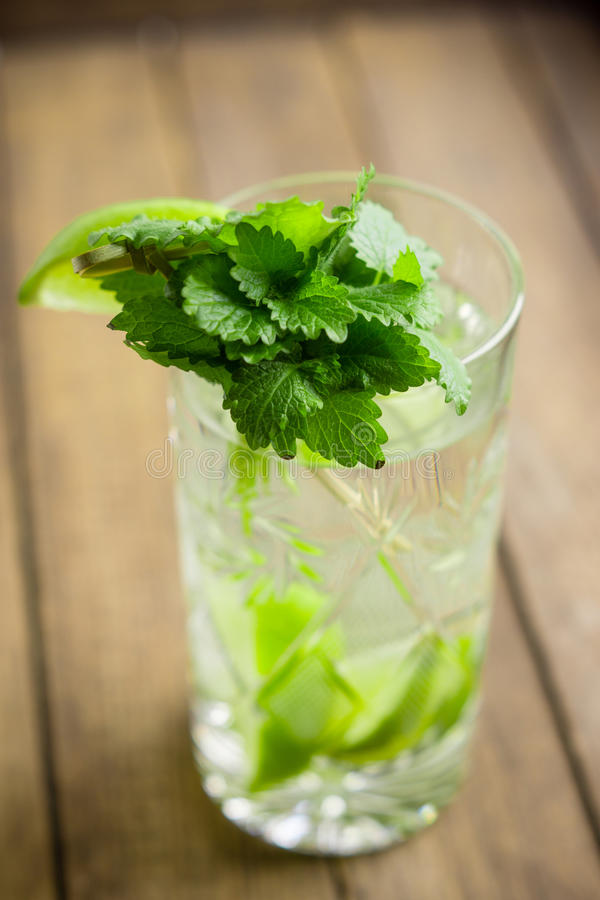 Fresh cocktail with mint. On the wooden background royalty free stock image