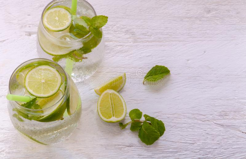 Fresh cocktail Mojito with ice lemon, white rum and mint on a light coloured wooden rustic table stock images