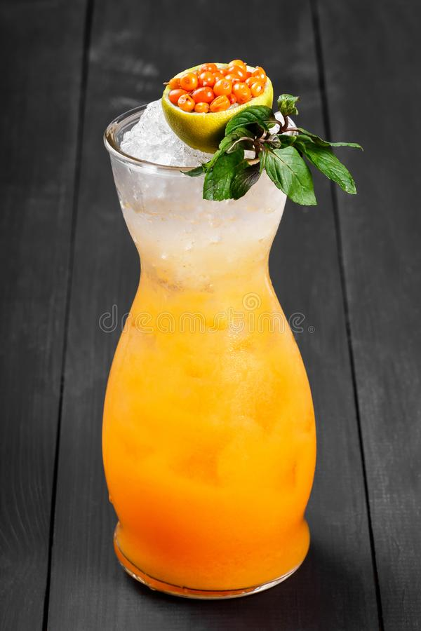 Fresh cocktail with sea buckthorn, juice, mint and ice in glass on dark background. Summer drinks and cocktails stock photography