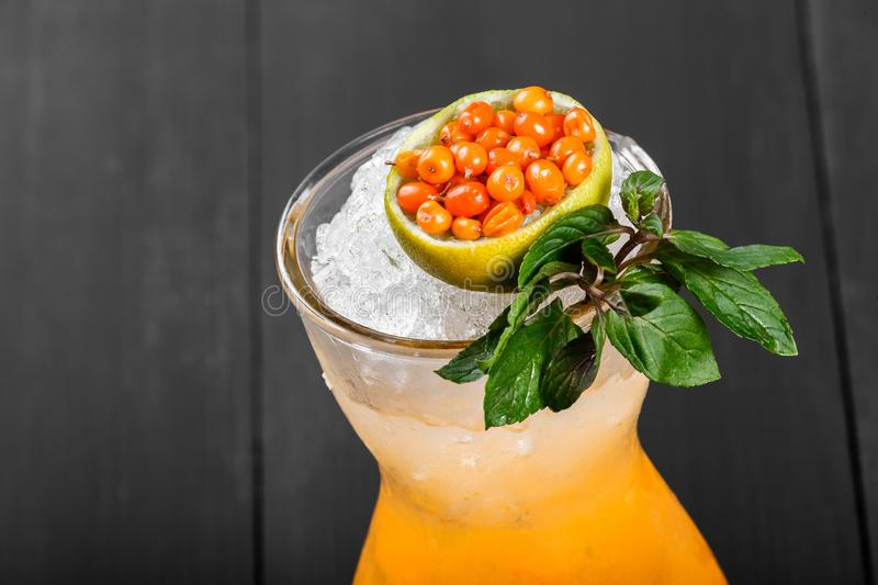 Fresh cocktail with sea buckthorn, juice, mint and ice in glass on dark background. Summer drinks and cocktails stock image
