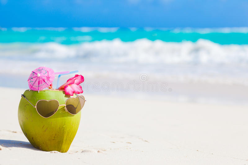 Fresh coconut cocktail on tropical beach with flower royalty free stock image