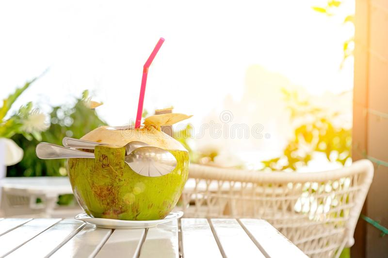 Fresh coconut juice with straw and two spoons on white wood table against blurred beach and mountain stock images