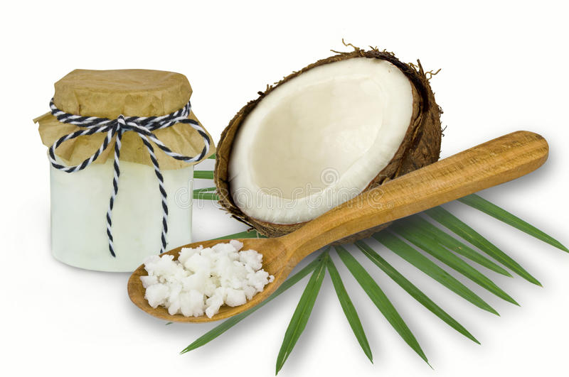 Fresh coconut oil in glassware and wooden spoon on a white backgroun.  stock images
