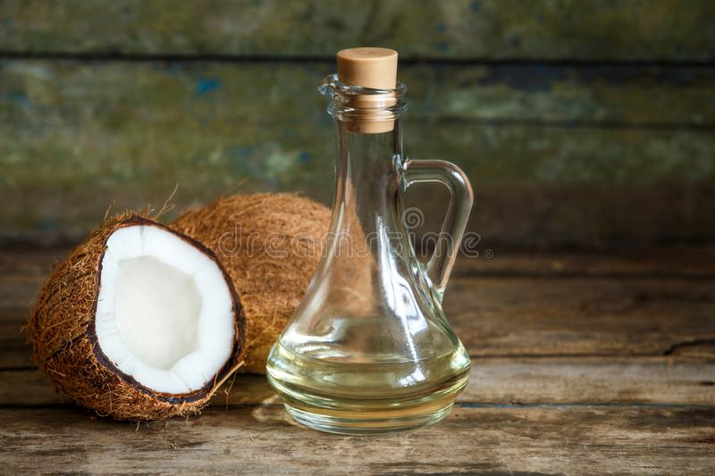 Fresh coconuts with coconut oil on wood background royalty free stock image