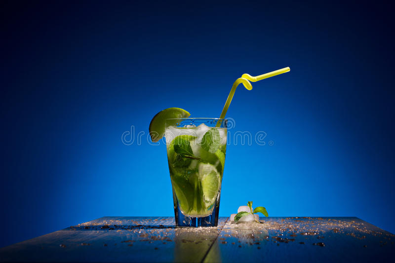 Fresh coctail with lime. Ice and mint on wooden table on blue background stock photo