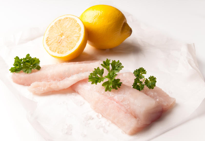 Fresh Cod Fillets. Fresh cod fish fillets with lemon and parsley on greaseproof paper royalty free stock photography