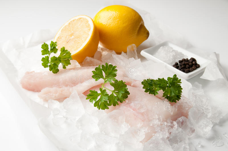 Fresh Cod Fillets. Of fish over crushed ice with parsley and lemon with salt and peppercorns stock images