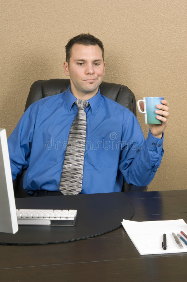 Fresh coffee. Young male office worker drinking his coffee at his computer with serious things on his mind royalty free stock image
