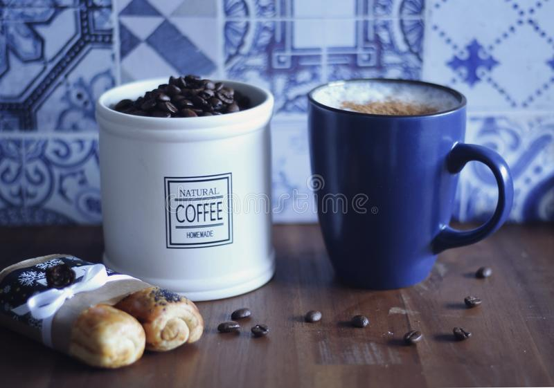 Fresh coffee beans with a delicious latte sprinkled with cinnamon and hungarian cookies royalty free stock images