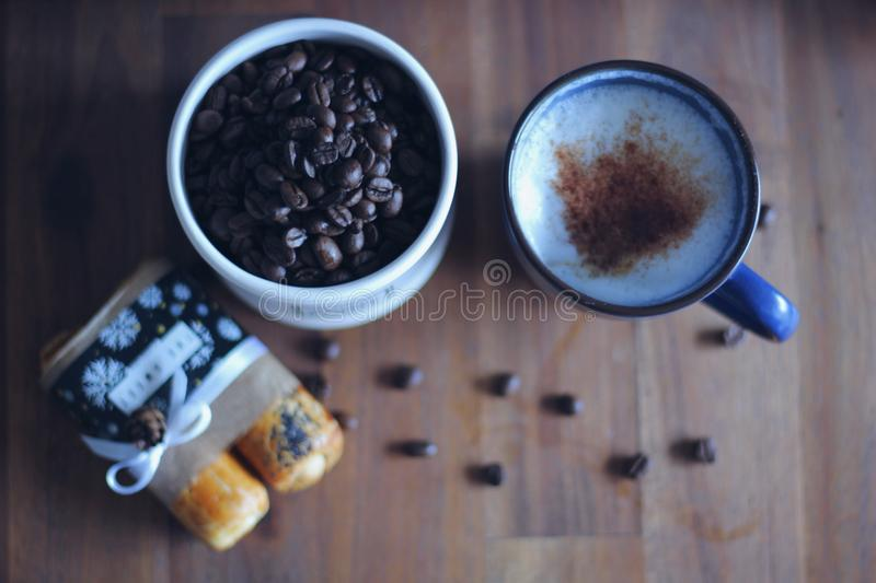 Fresh coffee beans with a delicious latte sprinkled with cinnamon and hungarian cookies royalty free stock photo