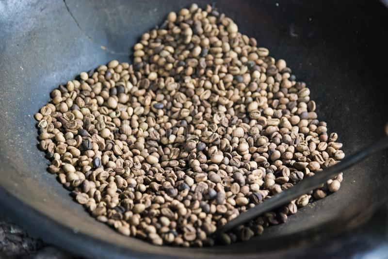 Fresh Coffee Beans - Freshly roasted 100 Arabica coffee beans falling into a spinning cooler professional machine. stock photo