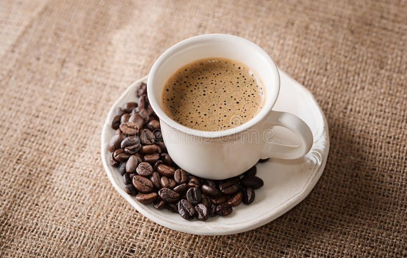 Fresh coffee and coffee beans on sackcloth stock image