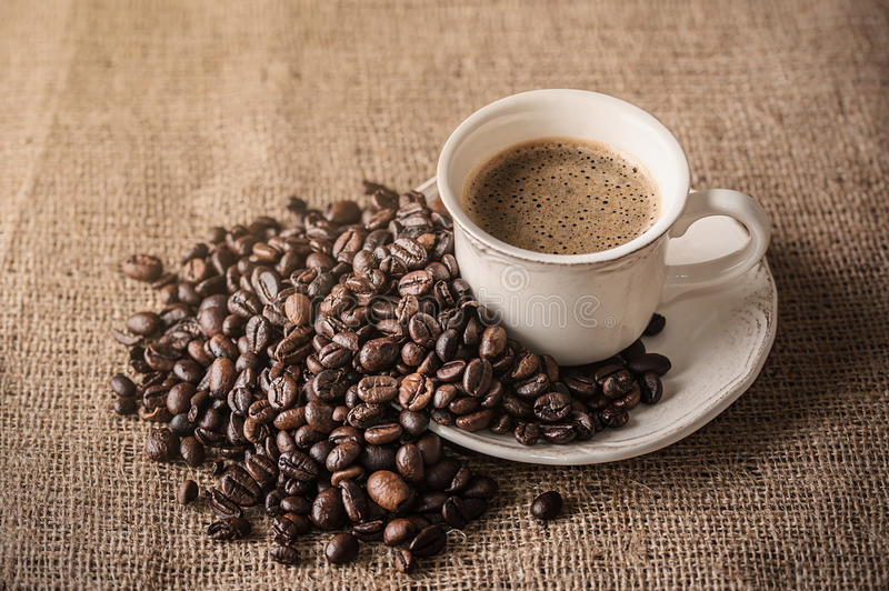 Fresh coffee and coffee beans on sackcloth stock photo